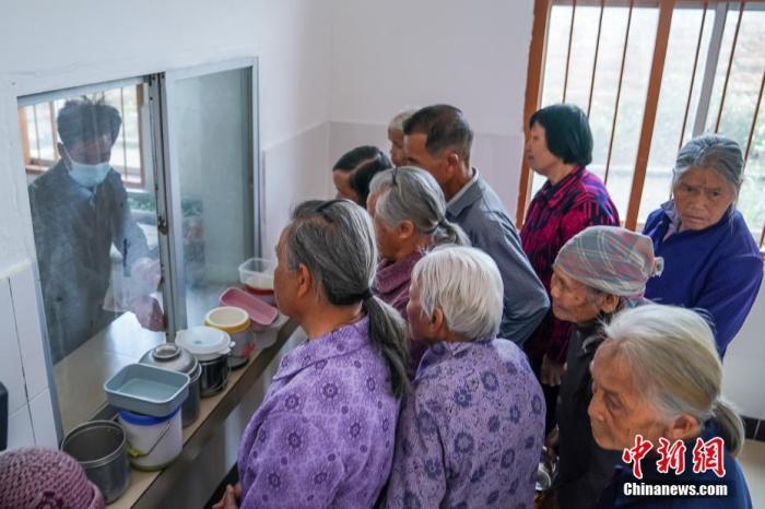 """资料图:广西隆安县东信村""""爸妈食堂""""内,老人们排队取餐。 <a target='_blank' href='http://www.chinanews.com/'><p  align="""
