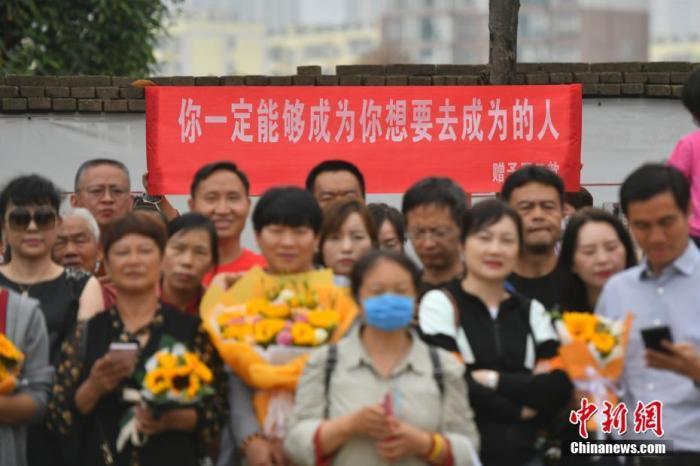 资料图:6月8日,云南省昆明市的考生结束2021年全国高考。图为考试结束后,一幅助考标语前有考生和家长合影留念。 <a target='_blank' href='http://www.chinanews.com/'><p  align=