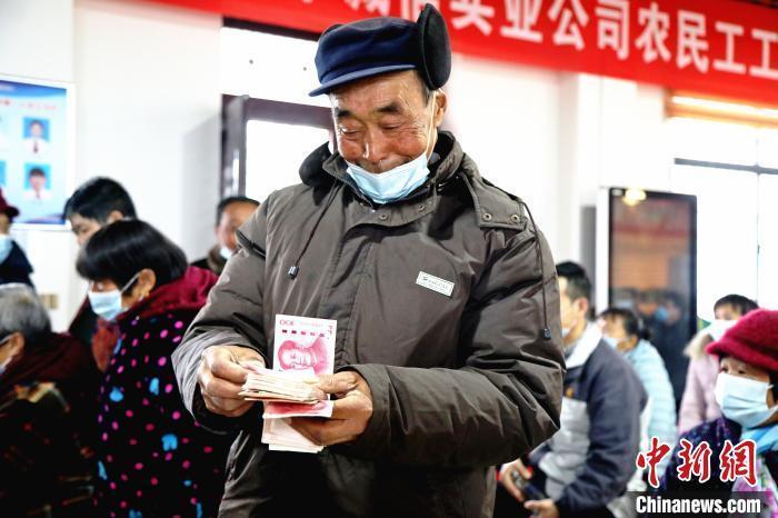 资料图:茶农数钱。 邱志烃 摄